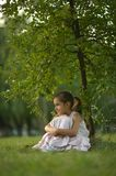 Little girl sitting under Royalty Free Stock Photos