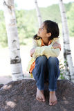Little girl sitting under trees Royalty Free Stock Image