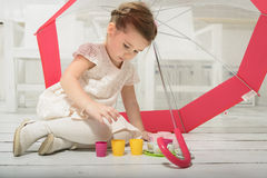 Little girl sitting under an umbrella having tea party Royalty Free Stock Images