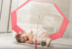 Little girl sitting under an umbrella Royalty Free Stock Photo