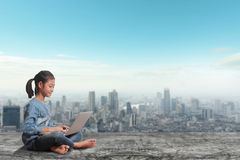 Little girl sitting using laptop computer on modern city skyline Royalty Free Stock Images