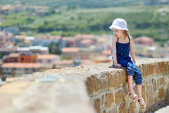 Little girl sitting on a wall enjoying a view Royalty Free Stock Image