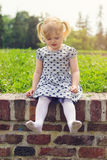 Little girl sitting on the wall, happy to be barefoot Stock Image