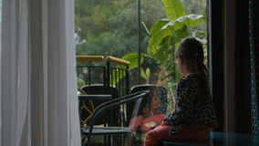 Little girl sitting and watching on the backyard from the inside. Wants to play but its heavy rain outside stock video footage