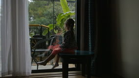 Little girl sitting and watching on the backyard from the inside. Wants to play but its heavy rain outside stock video