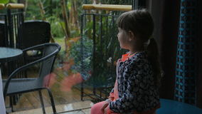 Little girl sitting and watching on the backyard from the inside. Wants to play but its heavy rain outside. Little girl sitting on the table and watching on the stock video