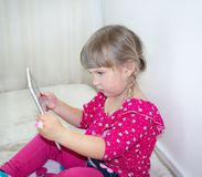 A little girl is sitting and watching cartoons on a tablet. NPlays on the tablet. A beautiful, white child royalty free stock photography