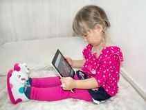 A little girl is sitting and watching cartoons on a tablet. NPlays on the tablet. A beautiful, white child stock image