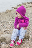 Little girl sitting. Little girl wearing a purple sweater sitting on a rock Stock Photography