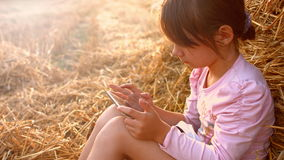 Little girl sitting in a wheat field on a haystack. A child playing with a tablet. 4K 30fps ProRes stock video