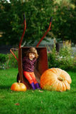 Little girl sitting in wheelbarrow with pumpkins Royalty Free Stock Image