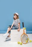 Little girl sitting on white boxes with tennis raquet and balls Stock Images