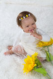 Little girl is sitting on the white carpet and laughs Stock Images