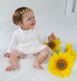 Little girl is sitting on the white carpet and laughs Royalty Free Stock Photography