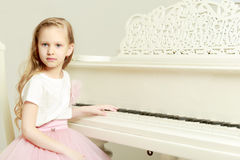 A little girl is sitting at the white piano. Royalty Free Stock Photos