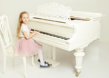 A little girl is sitting at the white piano. Stock Photo