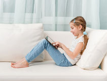 Little girl sitting on white sofa looks at tablet touching it. Profile photo Royalty Free Stock Images