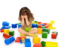 Little girl sitting on white among toys and crying Royalty Free Stock Photo