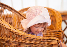 Little girl sitting in a wicker chair Royalty Free Stock Photo