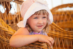 Little girl sitting in a wicker chair Royalty Free Stock Photography