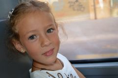 Little girl sitting by the window in the bus stock photography