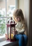 Little girl sitting by the window. Little girl sitting by the window with lantern Royalty Free Stock Image