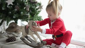 A little girl is sitting on the window next to the Christmas tree. She plays a beautiful porcelain horse. The baby is wearing a Santa Claus costume. Christmas stock video