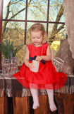 Little girl sitting by the window Stock Photos