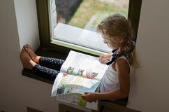 Little girl sitting by window and reading brochure Stock Image