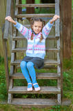 Little girl sitting on wooden Royalty Free Stock Images