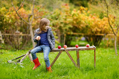 Little girl sitting on a wooden bench on autumn Stock Photo