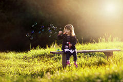 Little girl sitting on a wooden bench blows bubbles in the rays Royalty Free Stock Photography