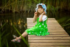 Little girl sitting on wooden bridge across river. In sunny summer day Royalty Free Stock Image