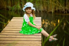 Little girl sitting on wooden bridge across river in summer day. Little girl sitting on wooden bridge across river in sunny summer day stock photography