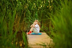 Little girl sitting on wooden bridge across river in summer day. Little girl sitting on wooden bridge across river in sunny summer day royalty free stock image
