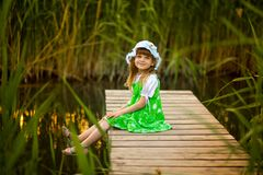 Little girl sitting on wooden bridge across river. In sunny summer day Royalty Free Stock Photos