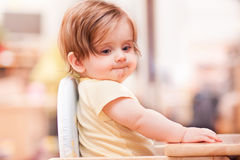 Little girl sitting on a wooden chair Stock Photos