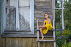 Little  girl sitting on a wooden ladder near a village house. Stock Photo