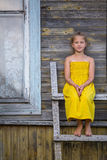 Little  girl sitting on a wooden ladder near a village house. Stock Image