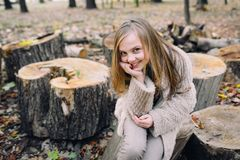 Little girl is sitting on wooden stump in the forest at autumn day. Close up Royalty Free Stock Photography