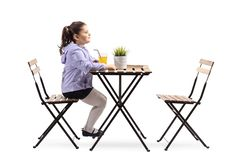 Little girl sitting at a wooden table with an empty chair stock images