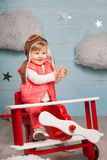 Little girl sitting in wooden toy plane Royalty Free Stock Photos