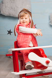 Little girl sitting in wooden toy plane Royalty Free Stock Image