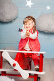 Little girl sitting in wooden toy plane Stock Photography