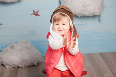Little girl sitting in wooden toy plane Royalty Free Stock Images