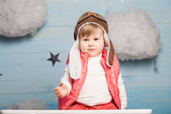 Little girl sitting in wooden toy plane Stock Photos