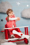 Little girl sitting in wooden toy plane Royalty Free Stock Photo