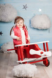 Little girl sitting in wooden toy plane Stock Images