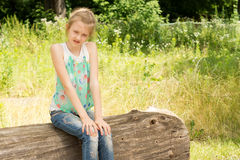 Little girl sitting in woodland on a log Stock Photos