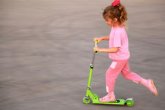Little girl skate on green scooter Royalty Free Stock Photo